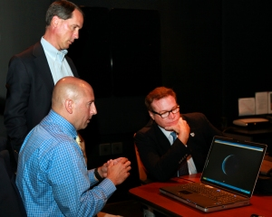 Detective Tom Evans of the Tennessee Internet Crimes Against Children Task Force (blue shirt) demonstrates child rescue technology to Tom Potok of Oak Ridge National Laboratory (standing) and PROTECT's David Keith